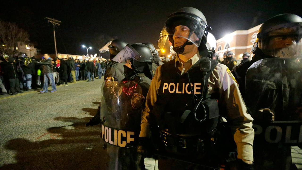 Police watch the street as protesters gather Tuesday, Nov. 25, 2014, in Ferguson, Mo.