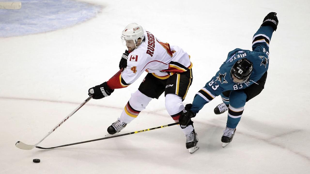 Calgary Flames defenseman Kris Russell (4) reaches for the puck next to San Jose Sharks left wing Matt Nieto during the second period of an NHL hockey game Wednesday, Nov. 26, 2014
