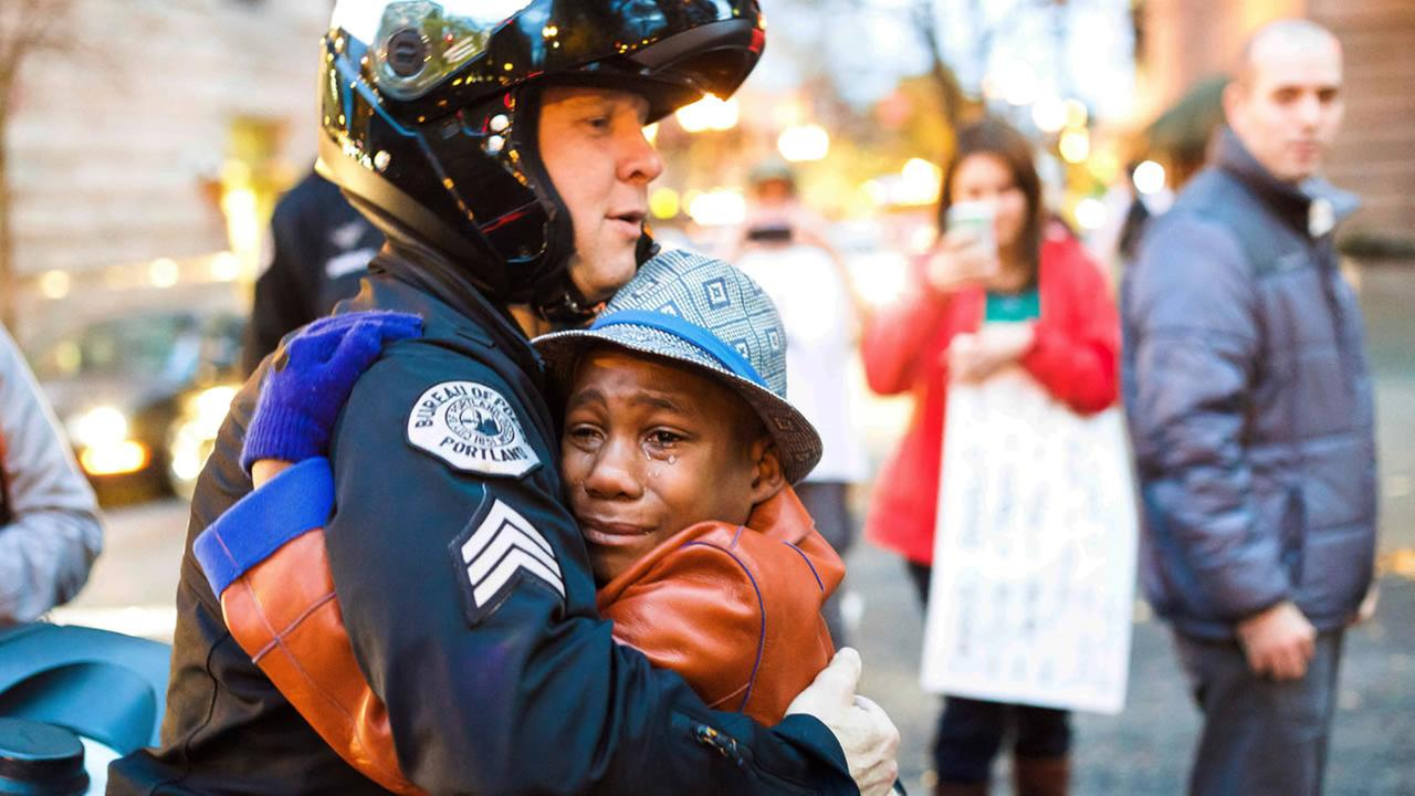 Portland police Sgt. Bret Barnum and Devonte Hart hug at a rally in Portland, Ore., where people gathered in support of the protests in Ferguson, Mo. (AP Photo/Johnny Huu Nguyen)
