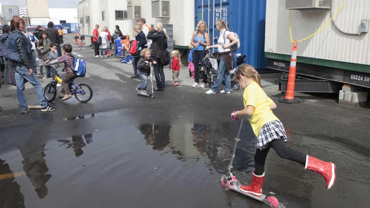 Kids riding scooters through a puddle of water in Boston. (AP Photo/Stephan Savoia)