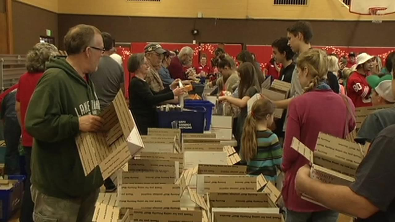 Bay Area volunteers packed boxes with clothing, toiletries, and cards to be sent to troops overseas who cant be with their families this holiday season.