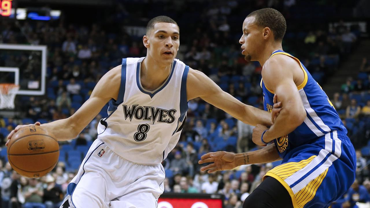 Minnesota Timberwolves guard Zach LaVine (8) pushes the ball down the court past Golden State Warriors guard Stephen Curry