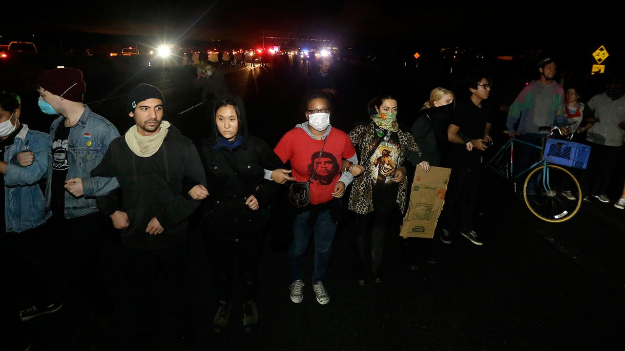 Protesters lock arms as they block traffic on Highway 80 in Berkeley, Calif., Monday, Dec. 8, 2014. in response to police killings in Missouri and New York. (AP Photo/Jeff Chiu)