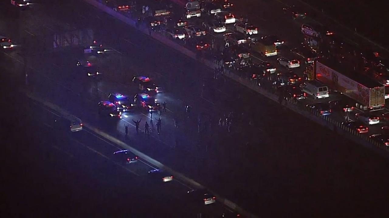 The CHP says a large group of demonstrators blocked traffic on both sides of Interstate 80 after destroying perimeter fencing and flooding lanes on Monday, Dec. 8, 2014.