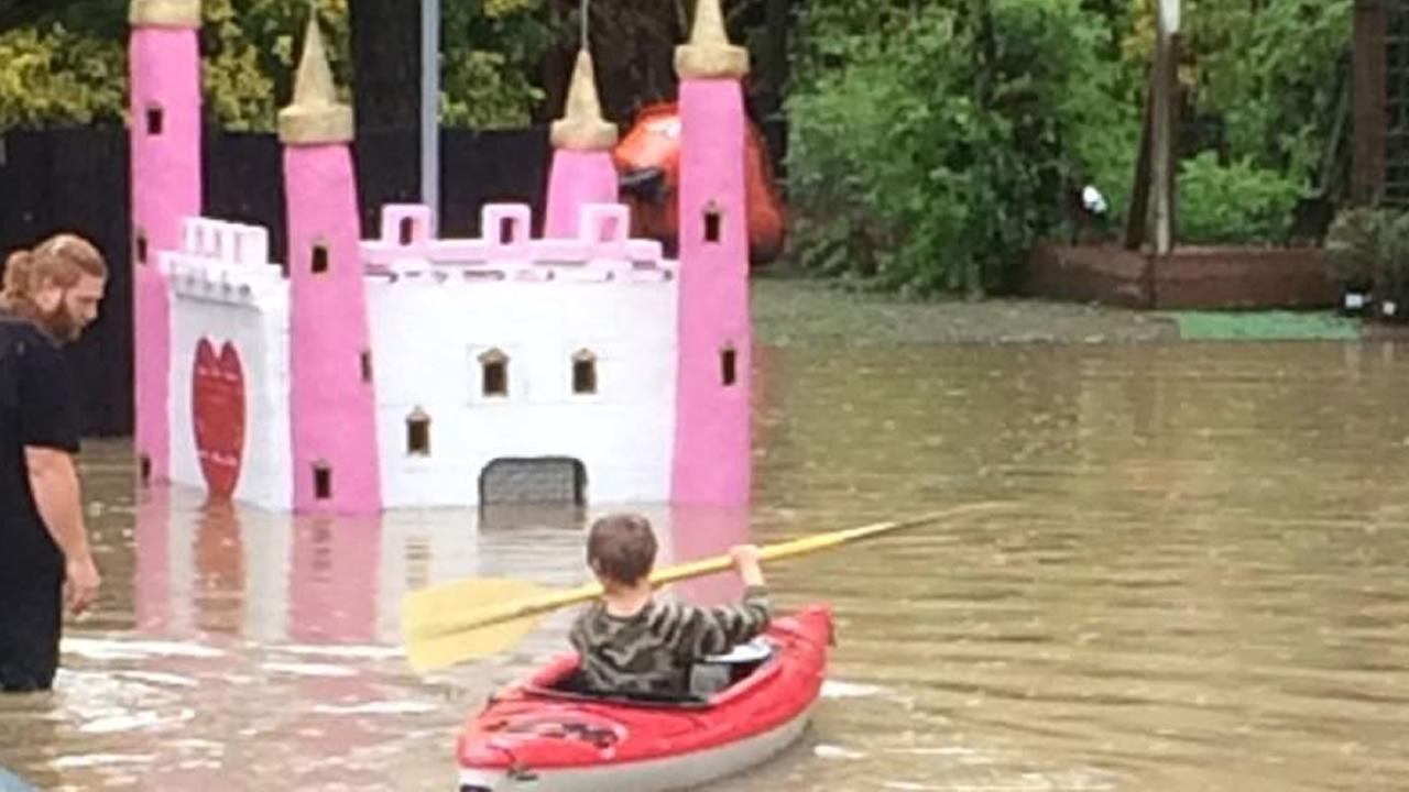 A child boats through the Pee Wee Golf course in Guerneville that is under water in the Russian River flooding.