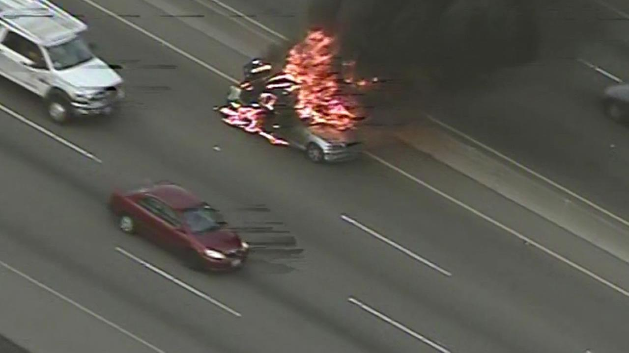 A car catches fire on I-880 near Hegenberger Road in Oakland.