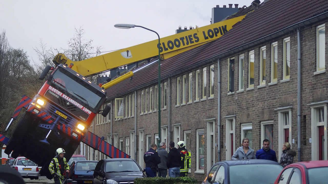 A crane which crashed into the roof of a house is seen following an unusual marriage proposal in the central Dutch town of IJsselstein, Dec. 13, 2014. (AP Photo/AS Media)
