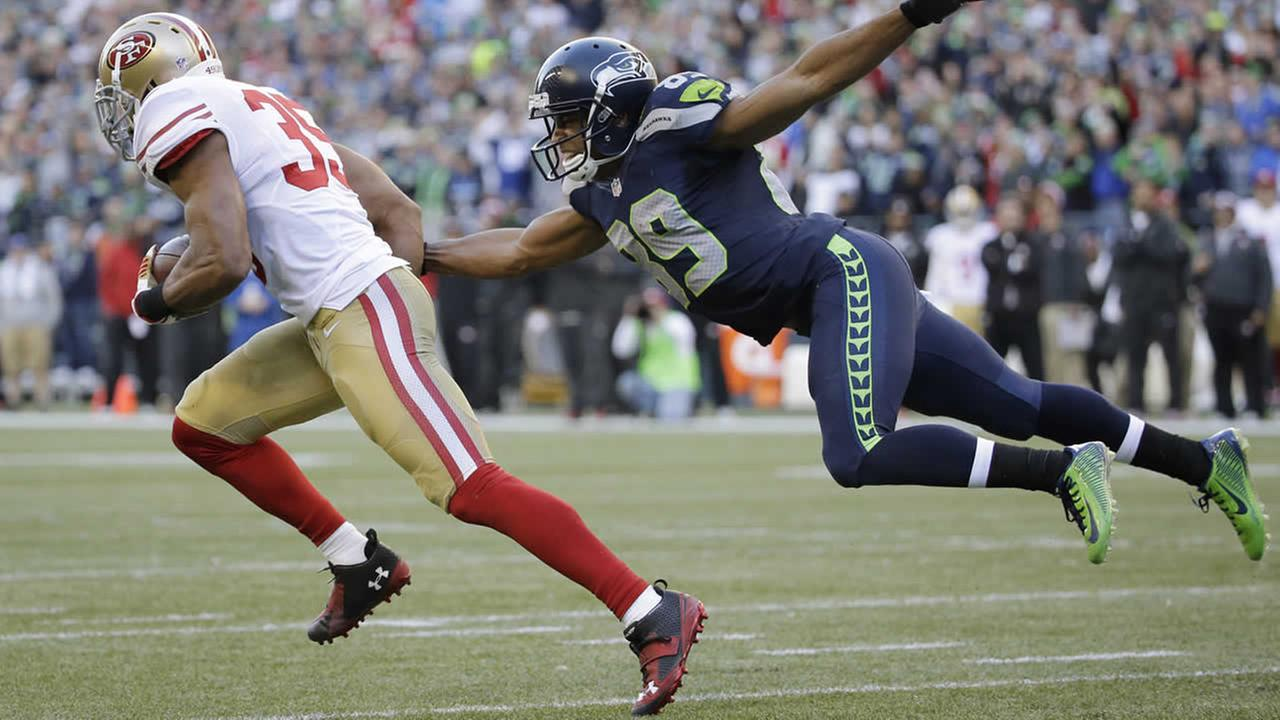 Seattle Seahawks wide receiver Doug Baldwin (89) tries to tackle San Francisco 49ers free safety Eric Reid (35) during a game, Dec. 14, 2014, in Seattle. (AP Photo/Elaine Thompson)