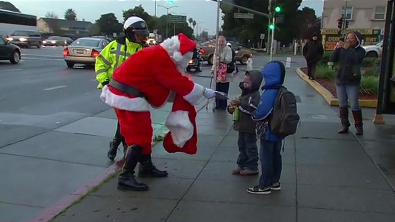 Motor Santa from the Oakland police department handed gifts to children in Oakland Wednesday.