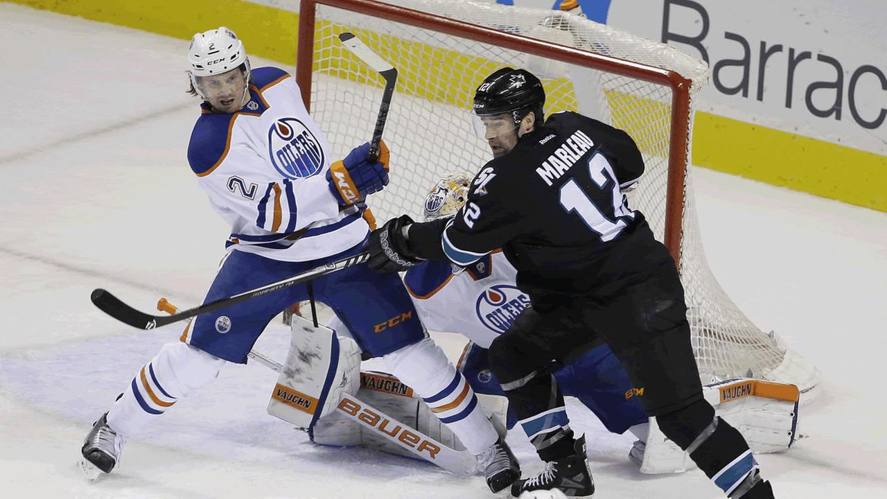 Edmonton Oilers defenseman Jeff Petry (2) and San Jose Sharks center Patrick Marleau (12) vie for the puck during the first period of an NHL hockey game Thursday,