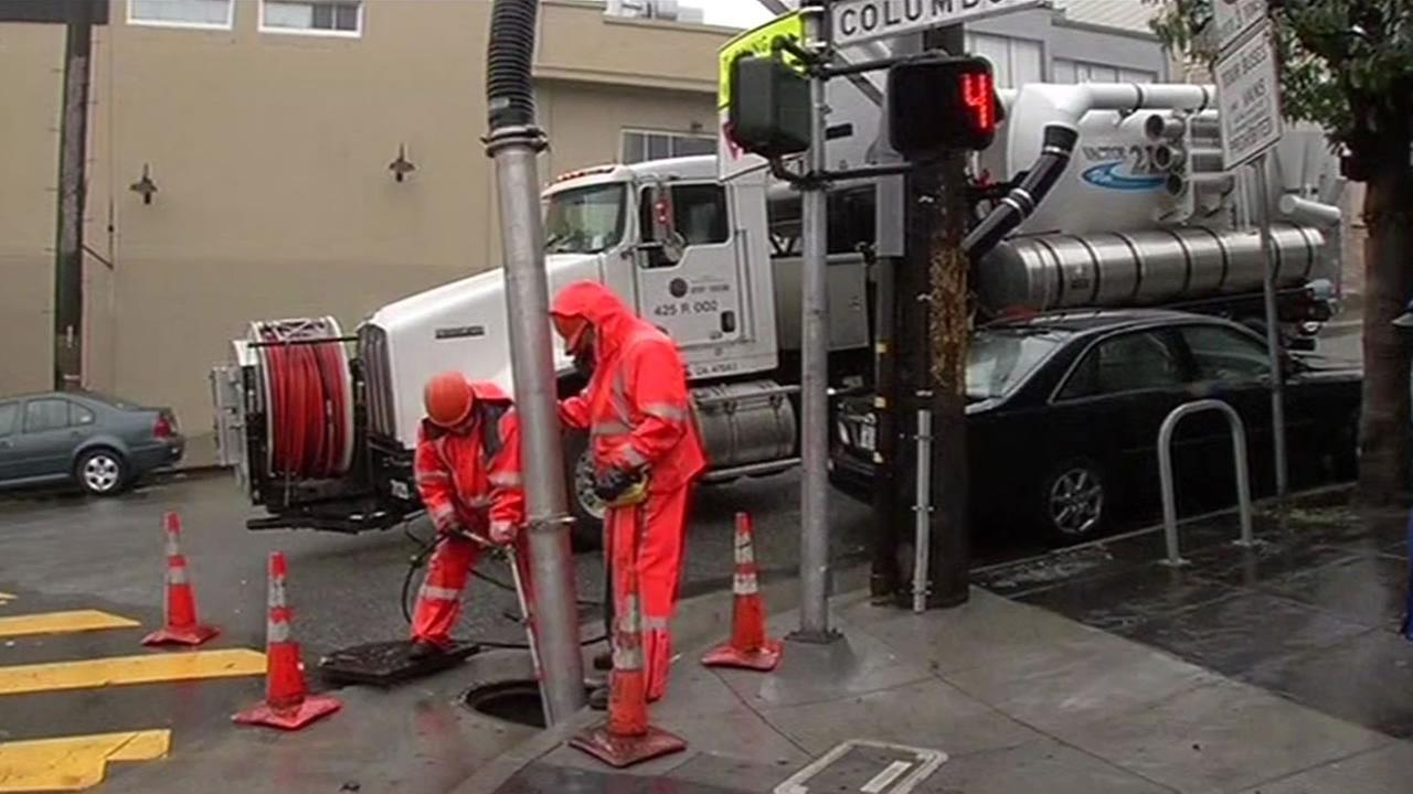 workers clean clogged drains