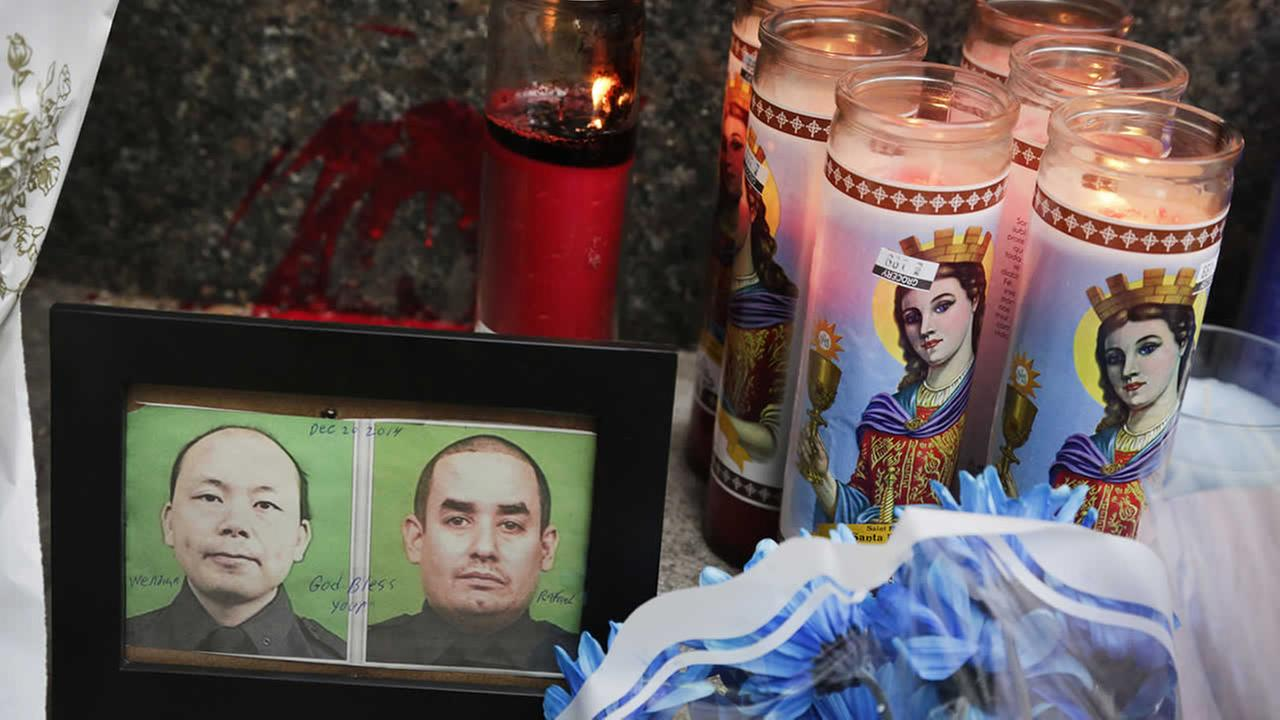 Photos of slain NYPD officers Wenjian Liu, left, and Rafael Ramos are placed in a memorial at the 84th Precinct in Brooklyn, where the officers were stationed, Dec. 21, 2014. (AP Photo/Mark Lennihan)