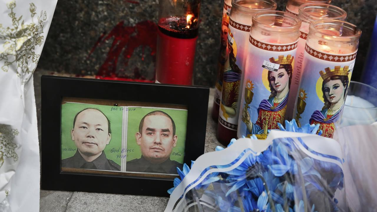 Photographs of slain New York Police officers Wenjian Liu and Rafael Ramos are placed in a makeshift memorial honoring the men in the Brooklyn on Sunday, Dec. 21, 2014. (AP Photo)