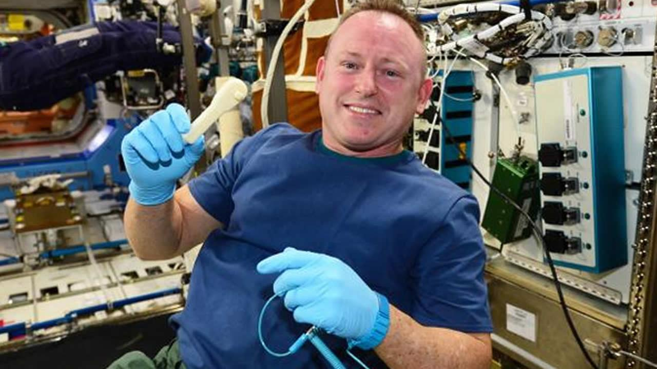 Commander Butch Wilmore shows off a wrench that was made with a 3-D printer in space.