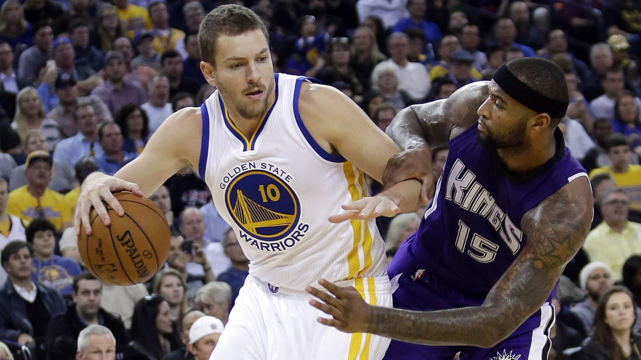 Golden State Warriors David Lee is defended by Sacramento Kings DeMarcus Cousins
