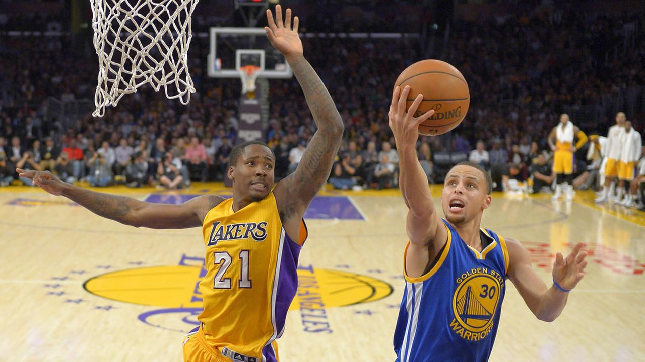 Golden State Warriors guard Stephen Curry, right, puts up a shot as Los Angeles Lakers forward Ed Davis defends during the first half of an NBA basketball game.