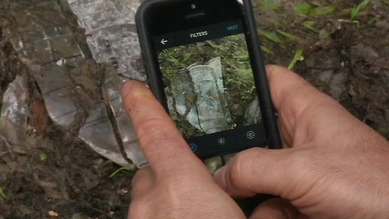 Man takes photo of trash with cellphone