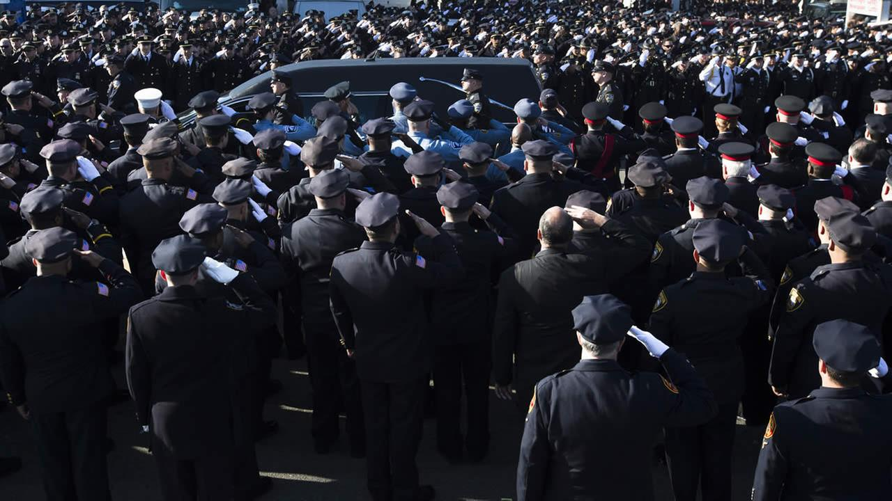 Officers salute as the hearse of NYPD Officer Rafael Ramos drives along his funeral procession route in Queens, Saturday, Dec. 27, 2014. (AP Photo/John Minchillo)