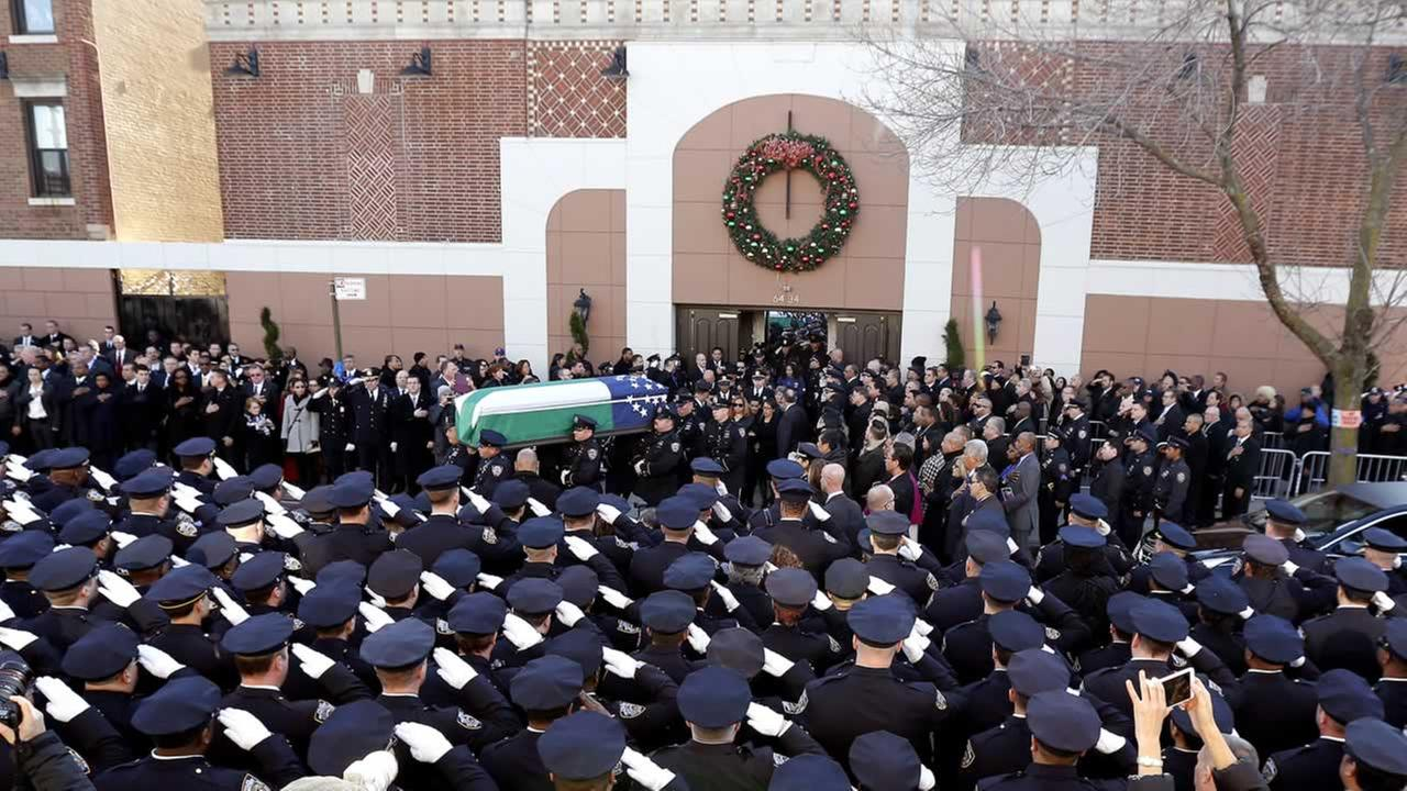 The casket of New York City police officer Rafael Ramos, center, is carried by pallbearers out of Christ Tabernacle Church.