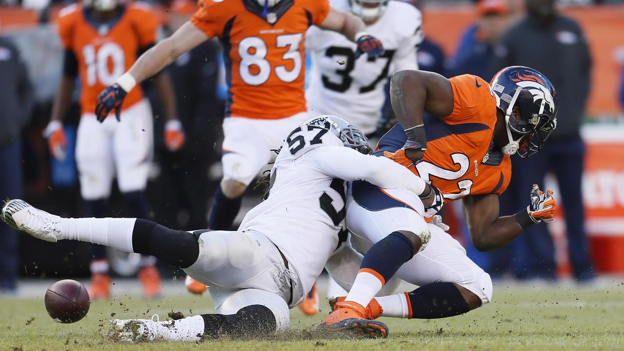 Raiders outside linebacker Ray-Ray Armstrong (57) forces Denver Broncos running back C.J. Anderson (22) to fumble during an NFL football game, Dec. 28, 2014, in Denver. (AP Photo)