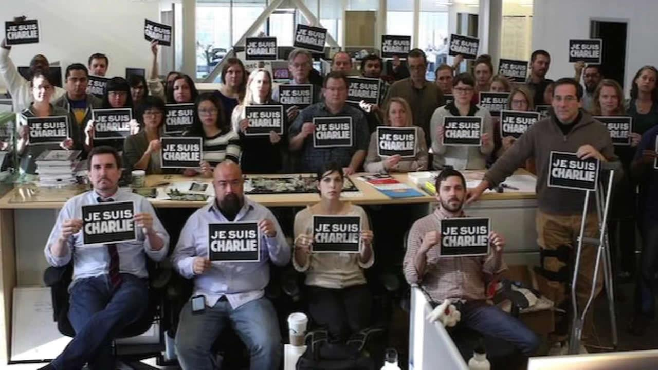 The Center for Investigative Reporting holds up signs in solidarity with the Paris terrorist attack victims on Wednesday, Jan. 7, 2015.