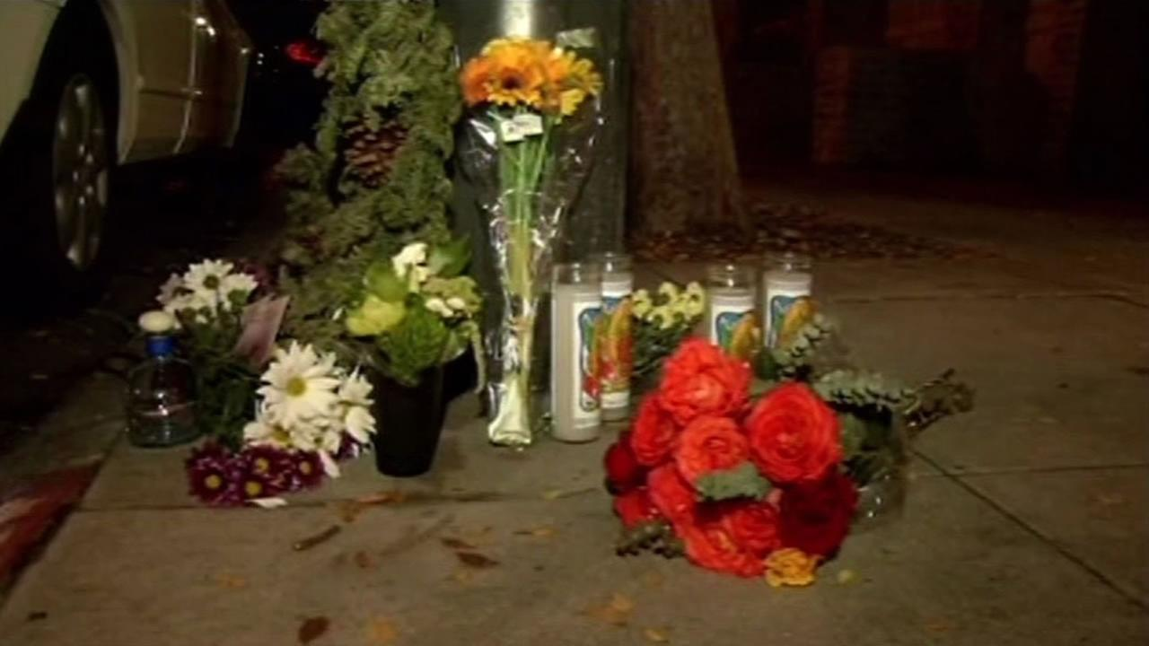 Flowers and candles have been placed at Hayes and Page in San Francisco, where four men were fatally shot on Friday, Jan. 9, 2015.