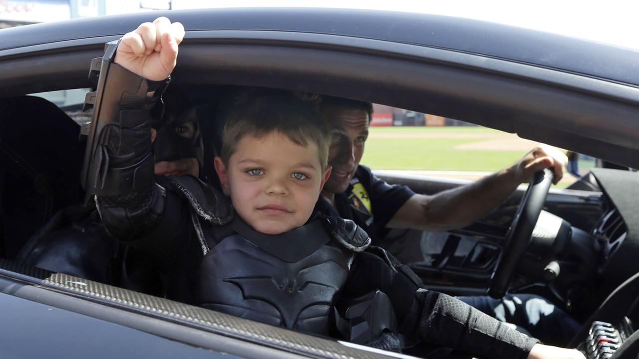 Miles Scott, dressed as Batkid, gestures as he sits in the Batmobile  in San Francisco, Tuesday, April 8, 2014. (AP Photo/Eric Risberg, Pool)