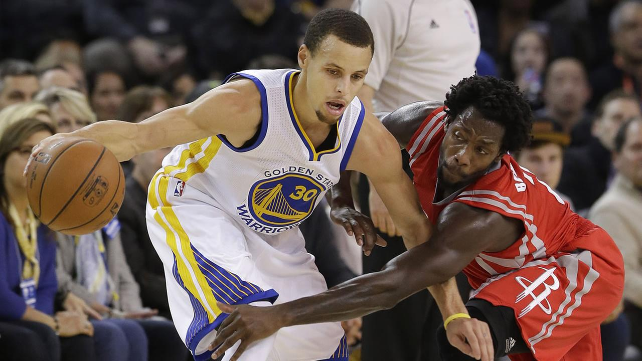 Golden State Warriors guard Stephen Curry (30) dribbles as Houston Rockets guard Patrick Beverley reaches for the ball during the first half of an NBA basketball game in Oakland.