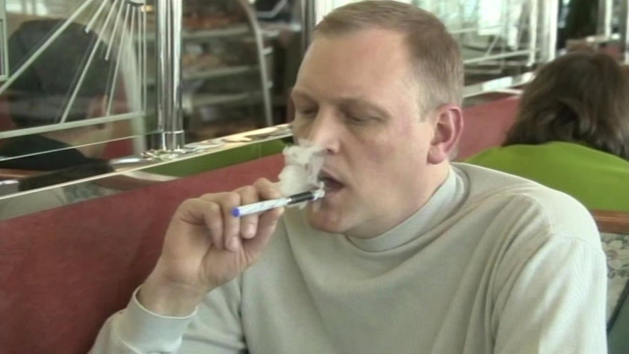 A man smokes an e-cigarette in a restaurant.