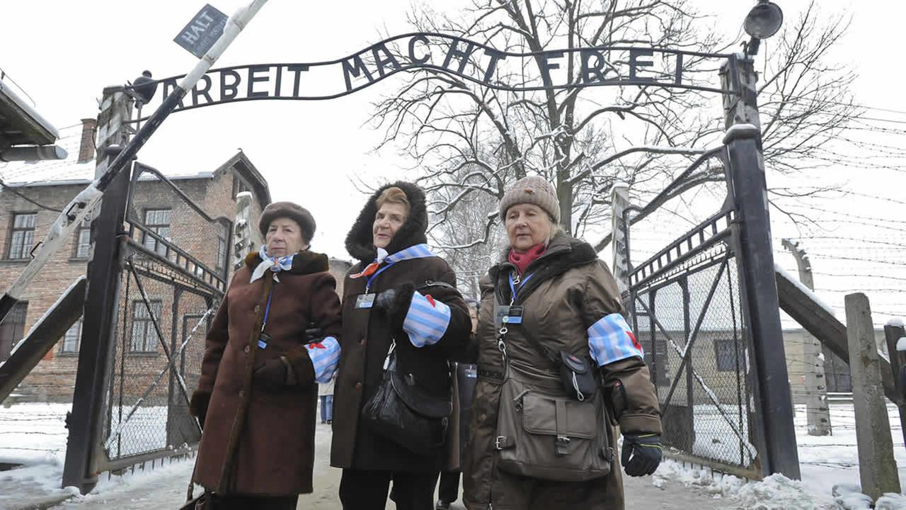 Holocaust survivors walk outside the gate of the of the Auschwitz Nazi death camp in Oswiecim, Poland, Tuesday, Jan. 27, 2015. (AP Photo/Alik Keplicz)