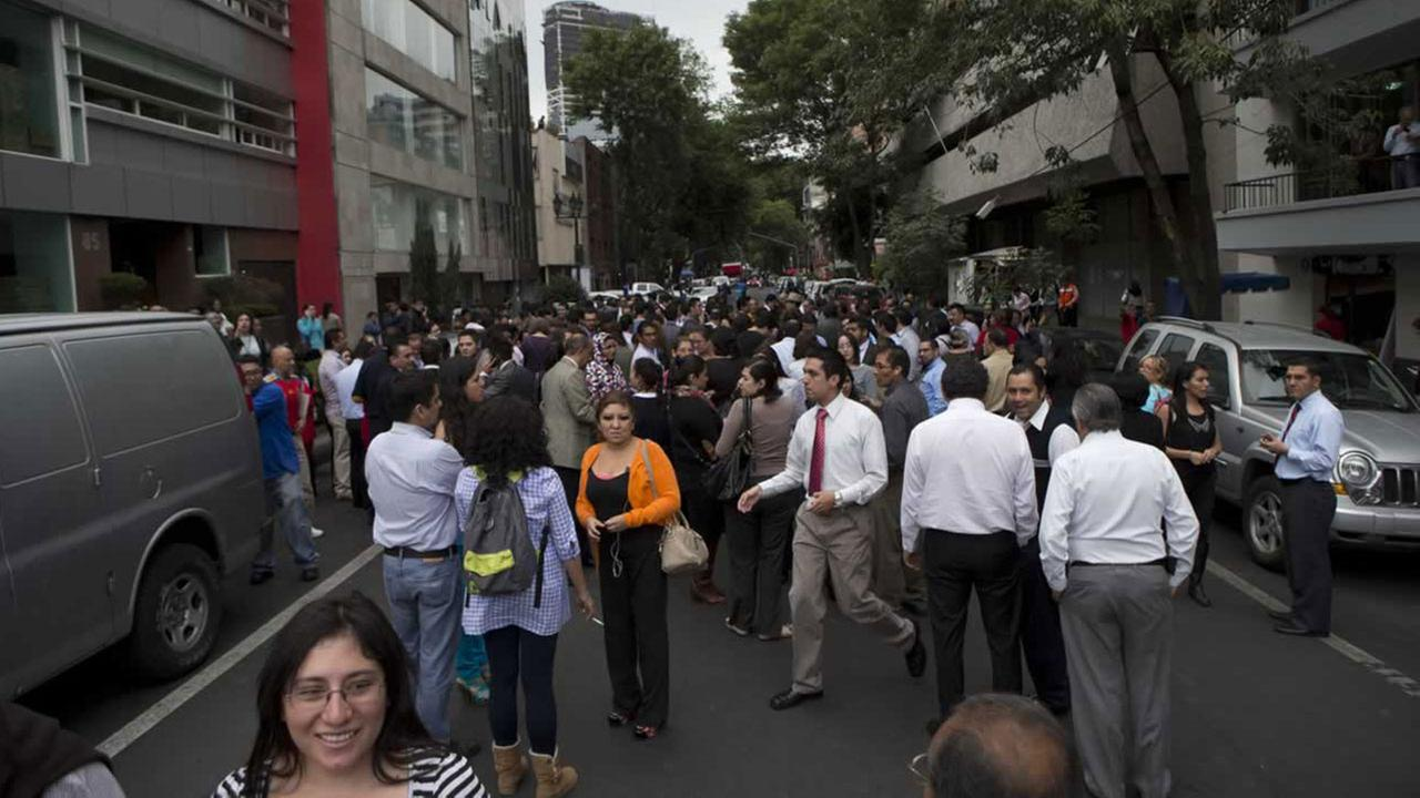 People gather in the street after an earthquake was felt in Mexico City, Thursday, May 8, 2014.