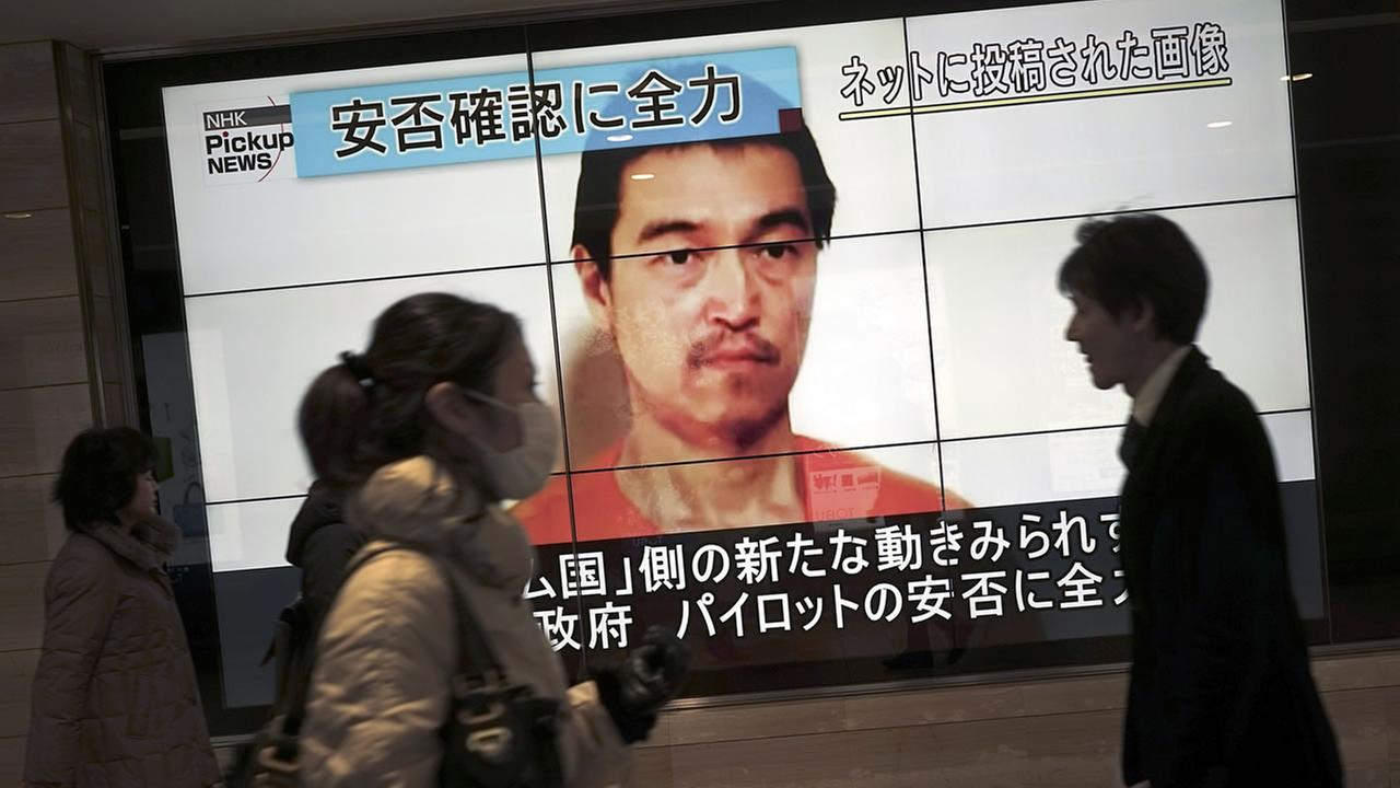 People walk by a screen showing TV news reports of Japanese hostage Kenji Goto, held by the Islamic State group, in Tokyo Saturday, Jan. 31, 2015. (AP Photo/Eugene Hoshiko)