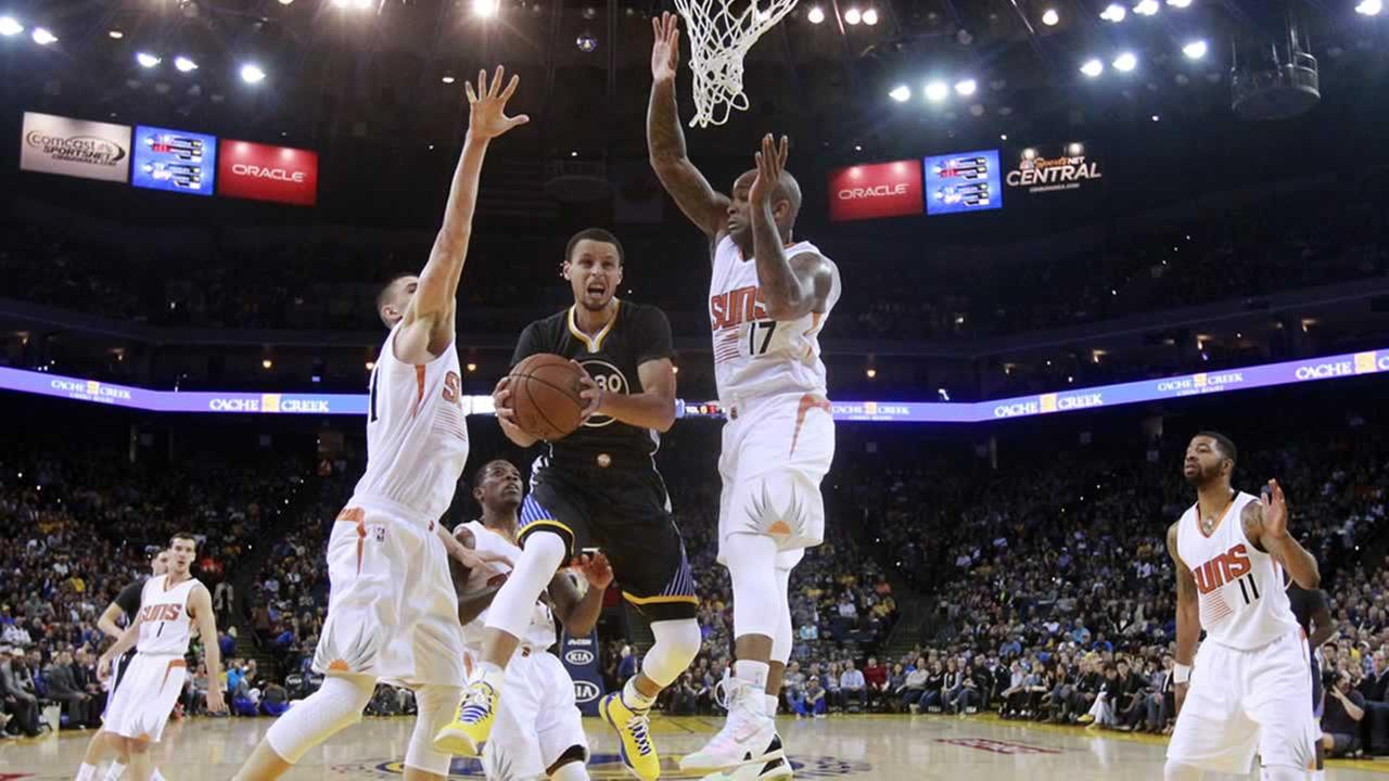 Warriors Stephen Curry, center, goes up for a shot between Phoenix Suns Alex Len, left, and P.J. Tucker on Saturday, Jan. 31, 2015, in Oakland. (AP Photo/Marcio Jose Sanchez)