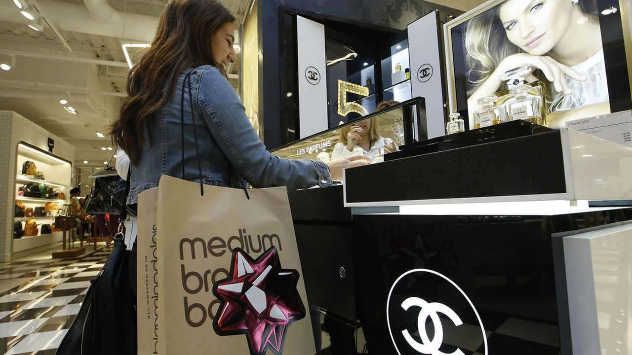 In this Nov. 28, 2014 file photo, a shopper buys Chanel perfume at a Bloomingdales store at the Glendale Galleria shopping mall in Glendale, Calif.  (AP Photo/Damian Dovarganes, File)