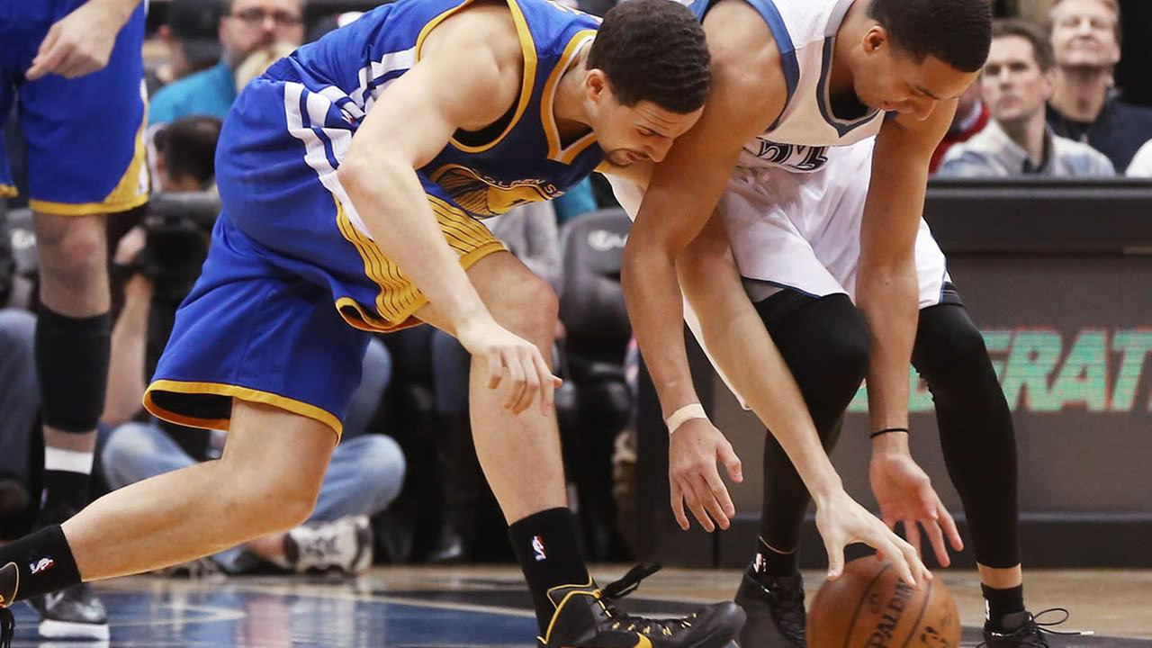 Golden State Warriors Klay Thompson, left, and Minnesota Timberwolves Kevin Martin chase the loose ball during a game, Wednesday, Feb. 11, 2015, in Minneapolis. (AP Photo/Jim Mone)