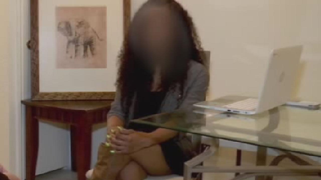 young woman sits during an interview, her face is blurred