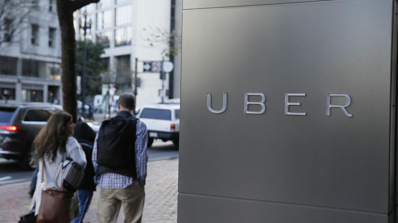 In this photo taken Tuesday, Dec. 16, 2014, a couple walks past the headquarters of Uber in San Francisco.