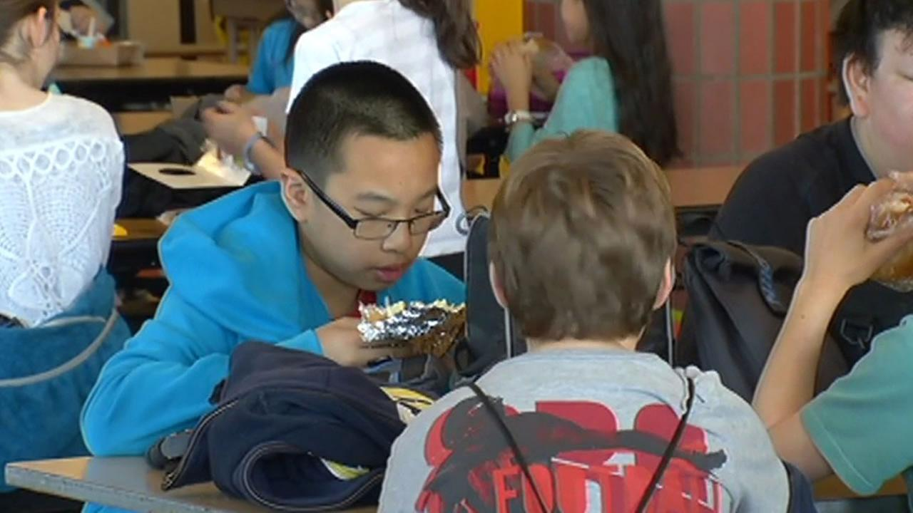 student eating lunch with other students