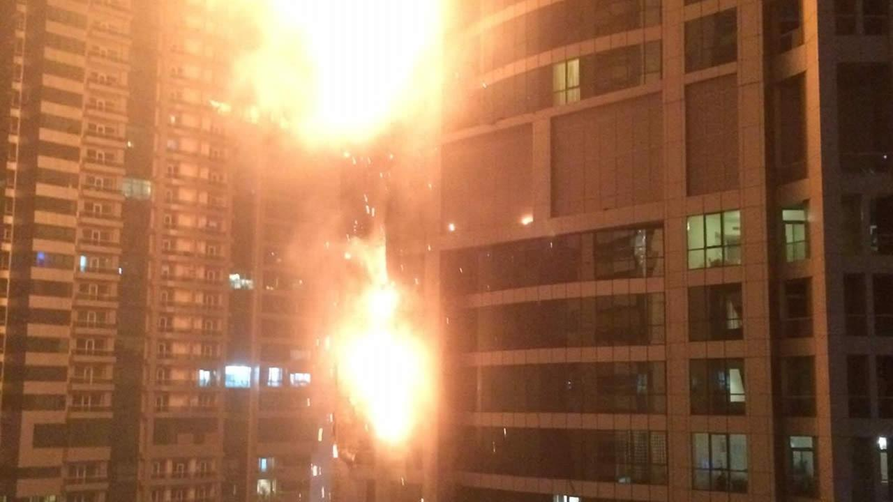 This photo provided by Rhea Saran shows flames coming from a high rise tower in Dubais marina district Saturday, Feb. 21, 2015. (AP Photo/Rhea Saran)