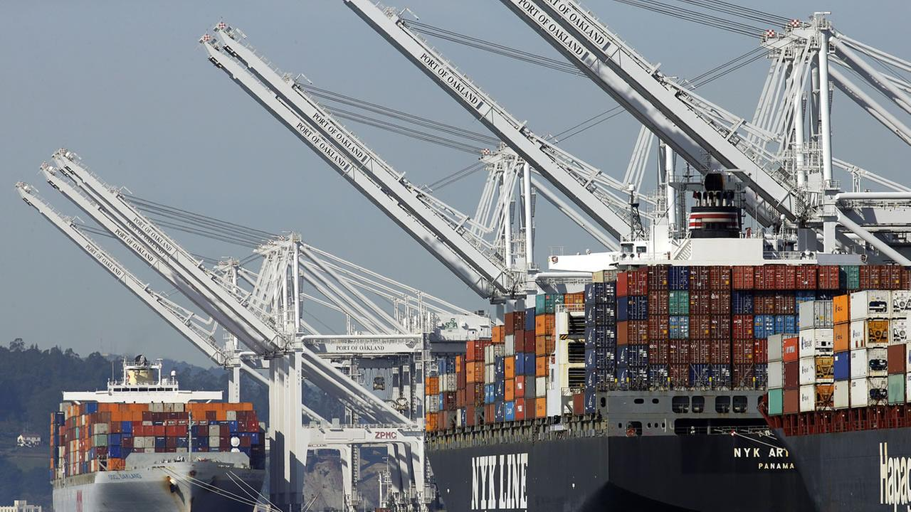 Container ships wait at the dock to be unloaded at the Port of Oakland Thursday, Feb. 12, 2015, in Oakland, Calif.
