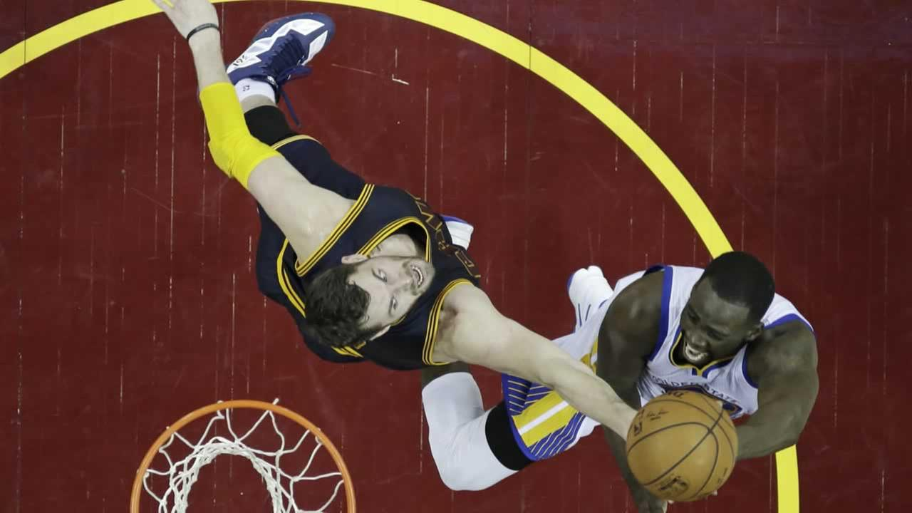 Golden State Warriors Draymond Green, right, drives to the basket against Cleveland Cavaliers Kevin Love