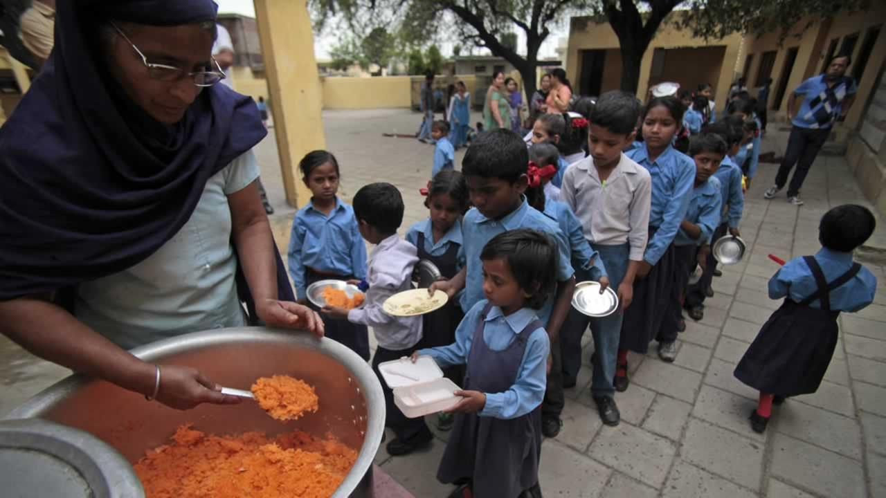 Children receive a free mid-day meal made of sweetened rice at a government school on the outskirts of Jammu, India.AP Photo/Channi Anand