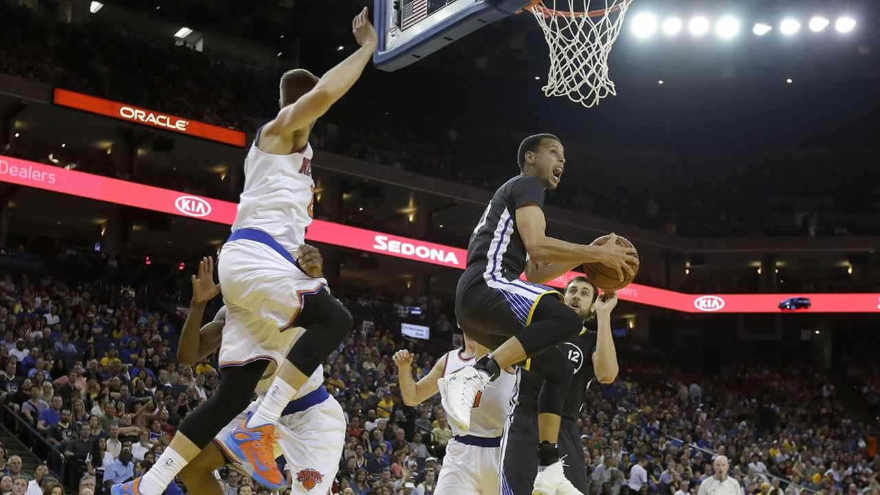 Golden State Warriors guard Stephen Curry, right, shoots against the New York Knicks during NBA basketball game in Oakland, Calif., Saturday, March 14, 2015.(AP Photo/Jeff Chiu)
