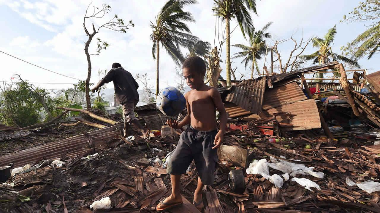 Samuel carries a ball through the ruins of their family home as his father, Phillip, at back, picks through the debris in Port Vila, Vanuatu after Cyclone Pam on March 16, 2015.  (AP Photo/Dave Hunt, Pool)