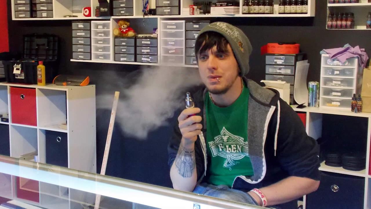 In this Jan. 13, 2015 photo, Tyler Newman, 24, vapes during his managing shift at the Madison, Wis., e-cigarette shop Infinite Vapor. (AP Photo/Dana Ferguson)