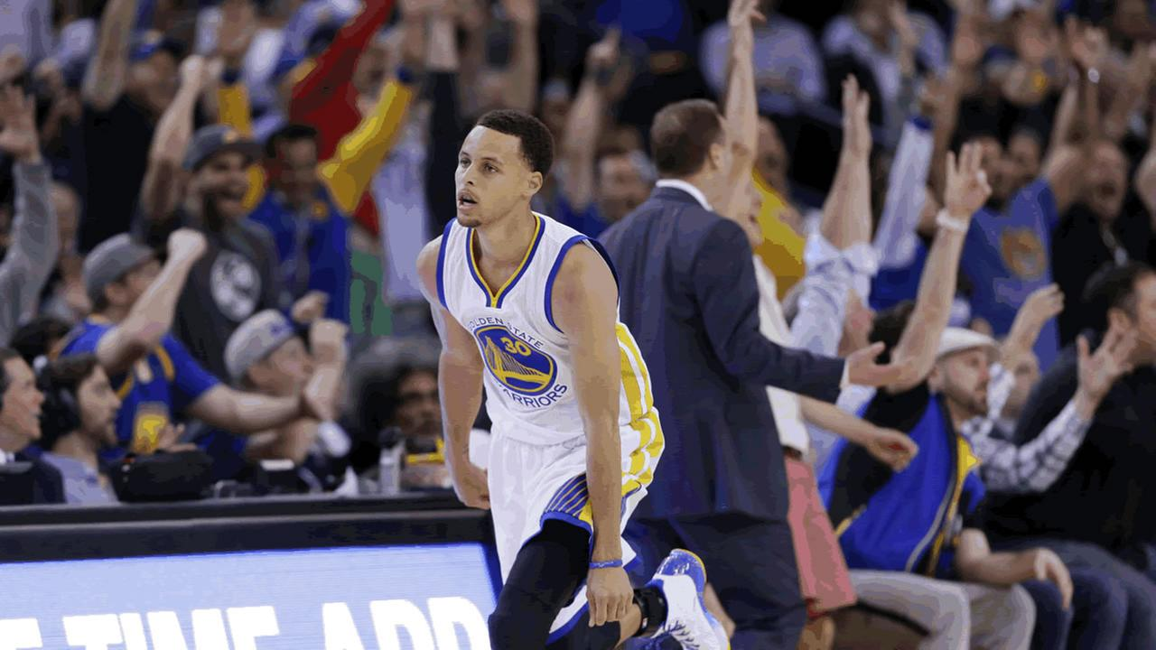 The crowd reacts as Golden State Warriors Stephen Curry, center, makes a three-point basket against the Atlanta Hawks during the first half of an NBA basketball game.