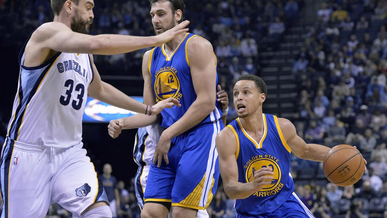 Golden State Warriors guard Stephen Curry gets assistance from Warriors center Andrew Bogut as he drives against Memphis Grizzlies on March 27, 2015. (AP Photo/Brandon Dill)