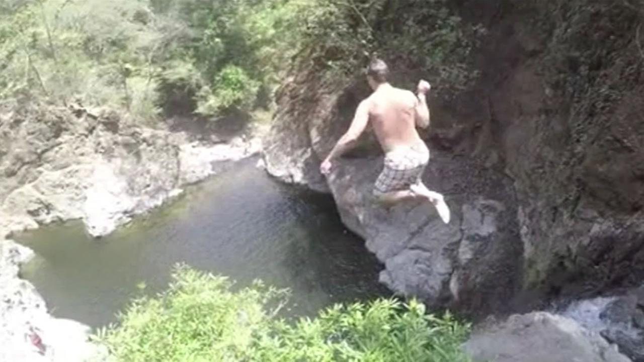 New England Patriots quarterback Tom Brady jumps off a cliff into a pool of water in Costa Rica.