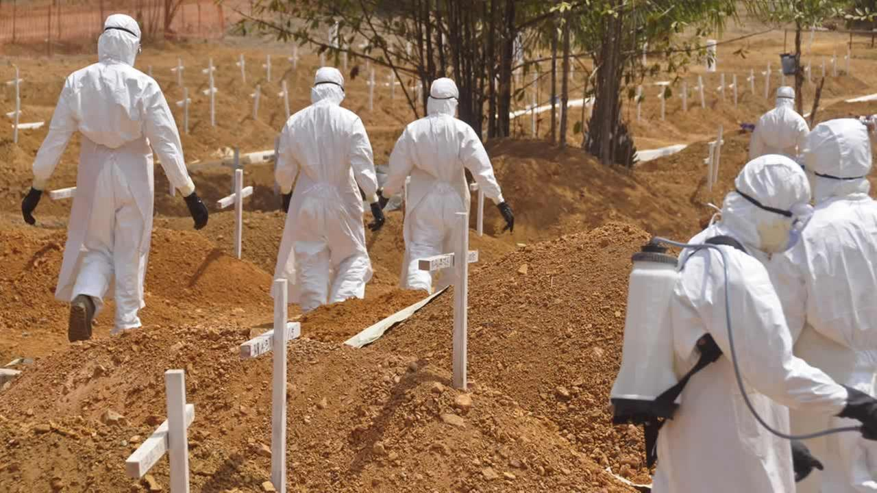 In this photo taken on March 11, 2015, health workers walk past graves after they buried a person that they suspect died from Ebola on the outskirts of Monrovia, Liberia. (AP Photo/Abbas Dulleh)