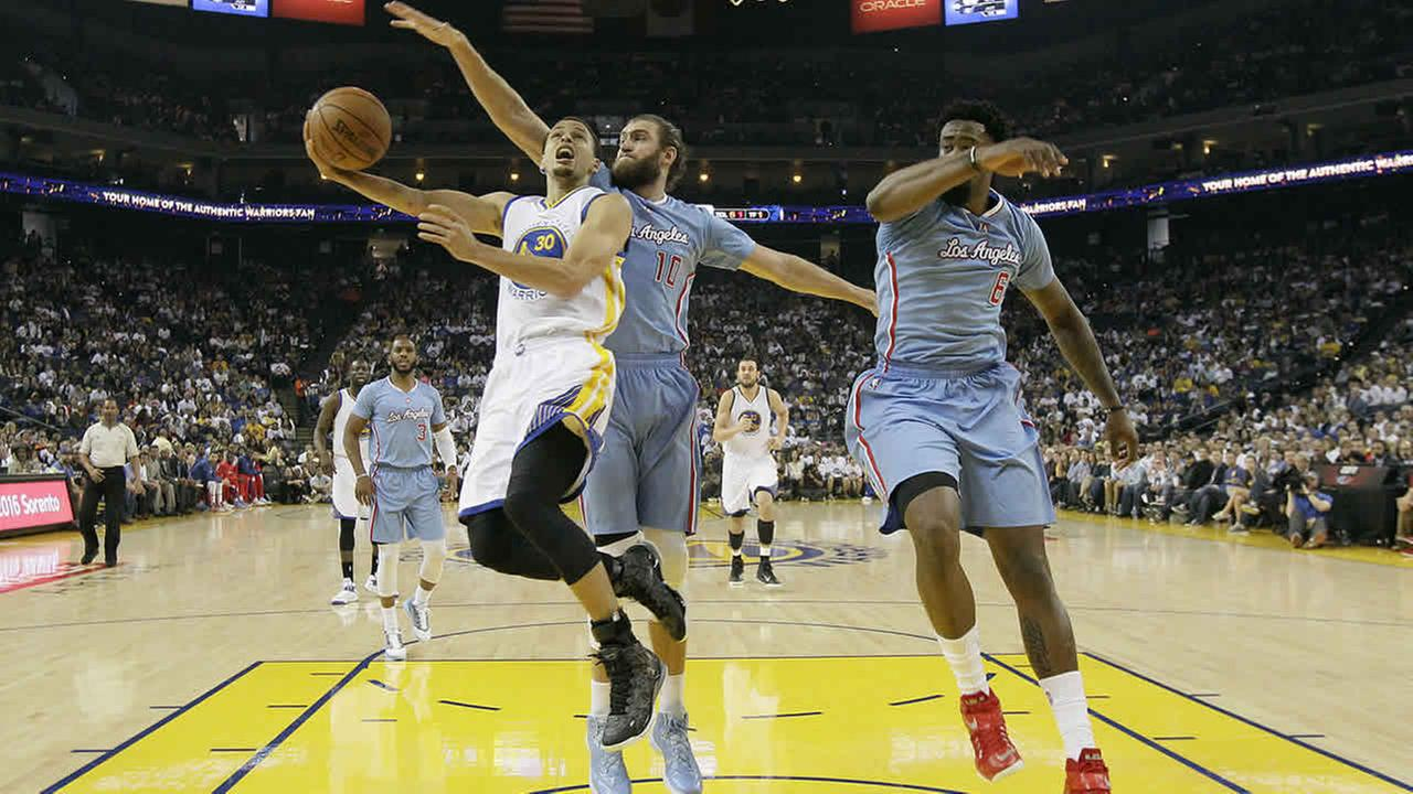 Golden State Warriors guard Stephen Curry shoots against Los Angeles Clippers forward Spencer Hawes and center DeAndre Jordan during a game in Oakland, Calif., March 8, 2015.  (AP Photo/Jeff Chiu)
